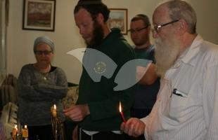 Mansbach familiy lighting historic menorah
