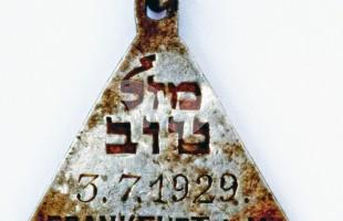 """The pendant with the Hebrew words """"Mazal Tov"""" and the date July 3, 1929"""