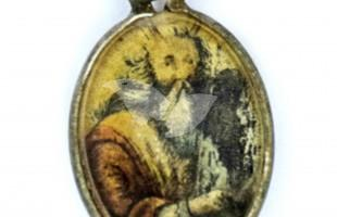A metal locket covered with glass with the image of Moses holding the Ten Commandments