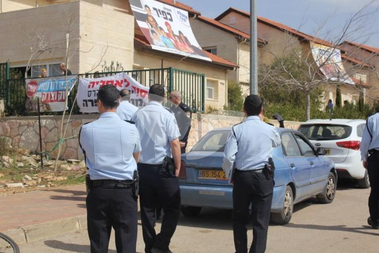 Police officers patrol the street of the nine houses in Ofra