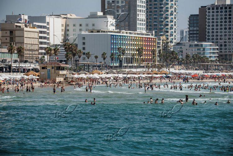 Israelis and tourists enjoy the beach in Tel Aviv